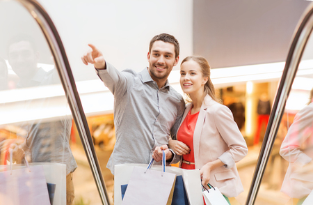 satisfied customer: sale, consumerism and people concept - happy young couple with shopping bags rising on escalator and pointing finger in mall