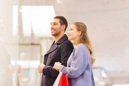 sale, consumerism and people concept - happy young couple with shopping bags looking to shopwindow in mall photo