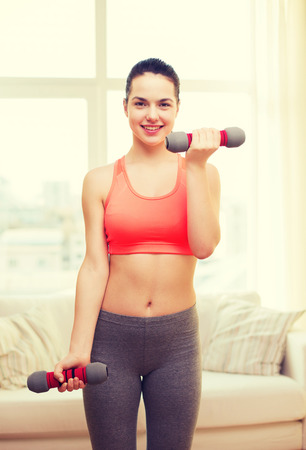 young woman sitting: fitness, home and diet concept - smiling redhead girl exercising with heavy dumbbells at home