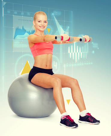 fit ball: fitness, exercise and diet concept - smiling sporty woman with dumbbells sitting on fitness ball
