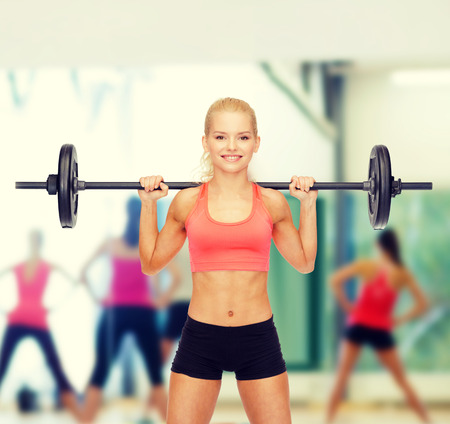 pumping: fitness, sport and dieting concept - smiling sporty woman exercising with barbell