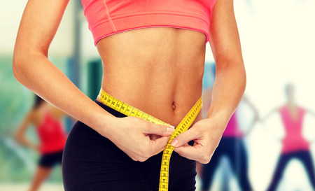 diet, sport, fitness and heath concept - close up of female hands measuring waist with measuring tape