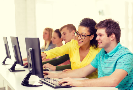 education, technology and school concept - smiling students in computer class at school Stock Photo