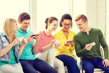 education, school and technology concept - smiling students with smartphone texting at school photo