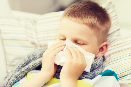 cold virus: childhood, healthcare and medicine concept - ill boy with flu blowing nose at home Stock Photo