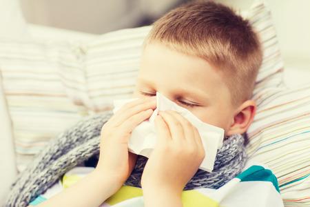 la infancia, la salud y concepto de la medicina - niño enfermo con la gripe que sopla la nariz en casa Foto de archivo