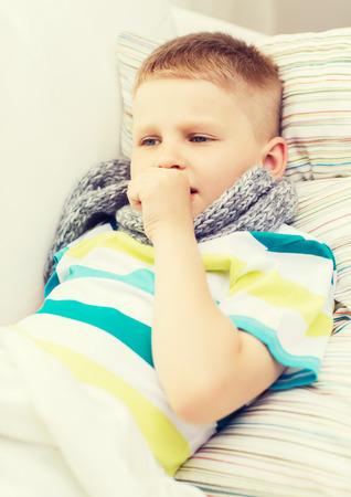 toser: la infancia, la salud y concepto de la medicina - niño enfermo con gripe tose en casa