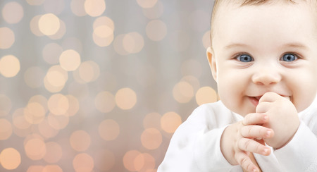 los niños, las personas, la infancia y concepto de la edad - hermoso bebé feliz durante las vacaciones luces de fondo