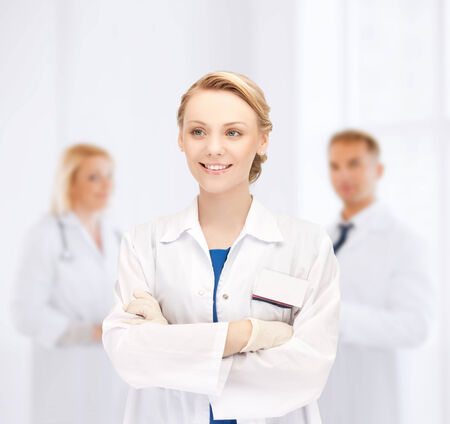 medicine, people, profession and teamwork concept - smiling young female doctor in white coat over group of medics in hospital photo