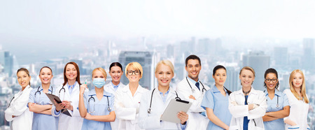 healthcare: healthcare, technology and medicine concept - smiling female doctors and nurses with tablet pc computer