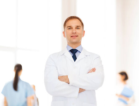 medics: healthcare, profession, teamwork and medicine concept - smiling male doctor in white coat over group of medics