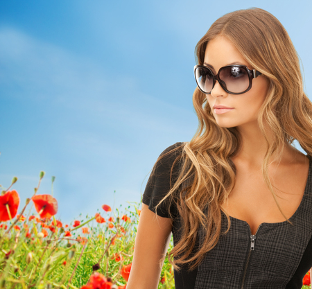 people, fashion, elegance and style concept - beautiful young woman in shades over blue sky and poppy field background photo