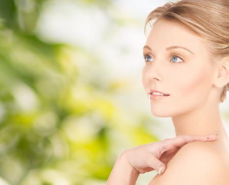 美しさと人々 のコンセプト - 緑の背景の上の美しい若い女性の顔 写真素材