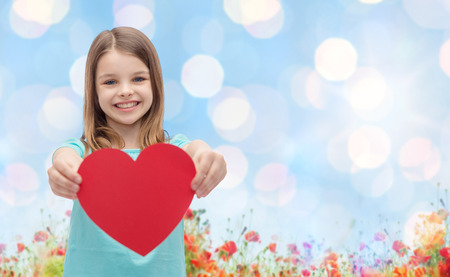 love, charity, holidays, children and people concept - smiling little girl with red heart over blue lights and poppy field background Фото со стока