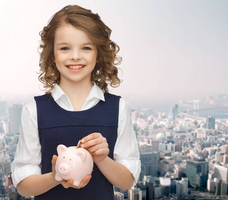 child charming: people, money, savings, investment and children concept - smiling girl putting coin into piggy bank over city background Stock Photo