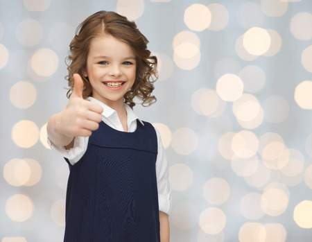 pre approval: people, gesture, children, summer vacation and happiness concept happy little school girl showing thumbs up over holidays lights background