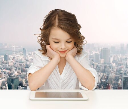 pretty preteen: people, technology, education and children concept - happy smiling girl with tablet pc computer over city background