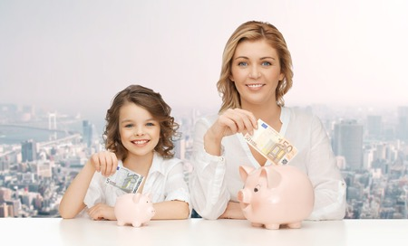 family budget: people, finances, family budget and savings concept - happy mother and daughter with piggy banks and paper money over city background