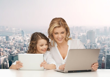 people, technology, family and parenthood concept - happy mother and daughter with laptop and tablet pc computers sitting at table over city background photo