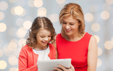 family, technology, people and christmas holidays concept - happy mother and daughter with tablet pc computer over lights background photo