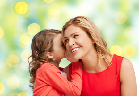 trust people: people, trust, love, family and motherhood concept - happy daughter whispering gossip to her mother over green lights background Stock Photo