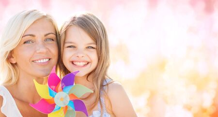 spinner: summer holidays, family, children and people concept - happy mother and girl with pinwheel toy over pink lights background Stock Photo