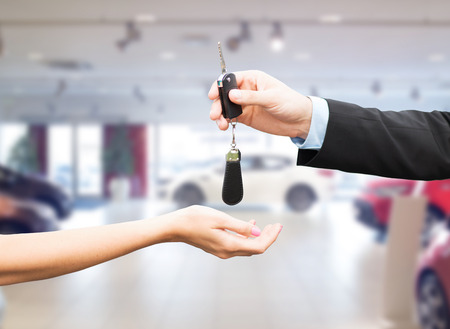 auto business, car sale, transportation, people and ownership concept - close up of car salesman giving key to new owner or customer over auto show background Stock Photo