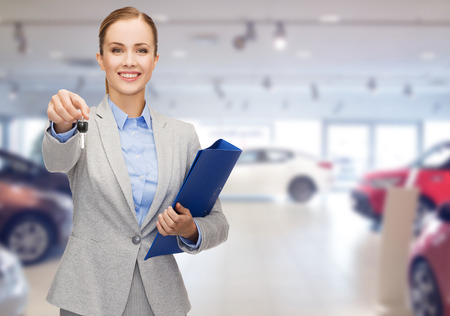 auto leasing: auto business, car sale, gesture and people concept - happy businesswoman or saleswoman with folder giving car key over auto show background Stock Photo