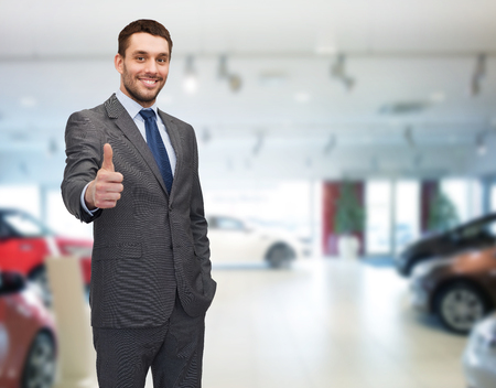 thumbs up business: auto business, car sale, gesture and people concept - smiling businessman showing thumbs up over auto show background