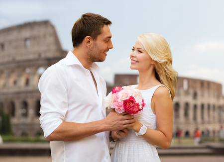 colosseum: summer holidays, travel, tourism, people and dating concept - happy couple with bunch of flowers over coliseum background Stock Photo