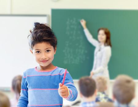 profesores: educaci�n, escuela primaria y los ni�os concepto - ni�a feliz estudiante con la pluma sobre el aula y profesor de escritura en fondo verde pizarra