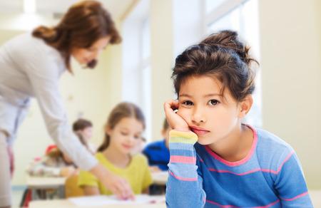 petite fille triste: l'�ducation, l'�cole �l�mentaire, les gens, l'enfance et les �motions notion - triste ou ennuy� petite fille des �l�ves au fil vert tableau � craie fond Banque d'images