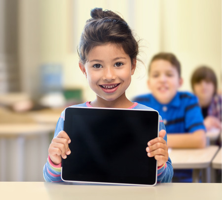 education, elementary school, technology, advertisement and children concept - little student girl showing blank black tablet pc computer screen over classroom and classmates background Фото со стока