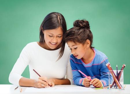 vzdělávání, škola, děti, tvořivost a šťastní lidé koncept - šťastná učitel a dívka kreslení přes zelené křídu palubě pozadí