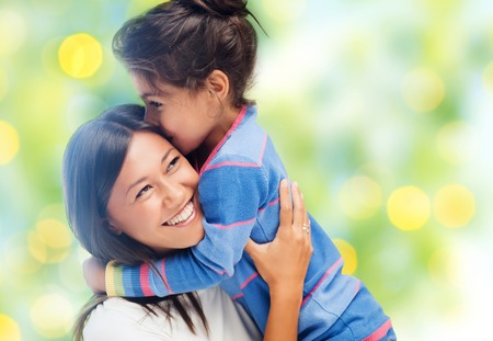 preteen asian: people, happiness, love, family and motherhood concept - happy mother and daughter hugging over green lights background