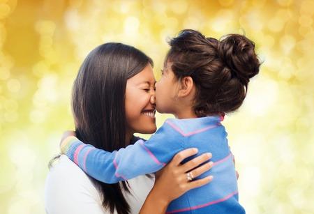 personas abrazadas: familia, los niños y la gente feliz concepto - una niña abrazando feliz y besa a su madre sobre las luces de fondo amarillo