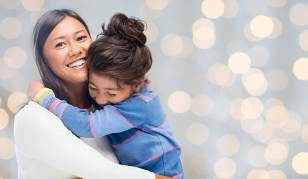 asian children: people, happiness, love, family and motherhood concept - happy mother and daughter hugging over holiday lights background Stock Photo