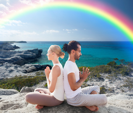 chakra: fitness, sport, people, yoga and lifestyle concept - happy couple meditating in lotus pose on summer beach