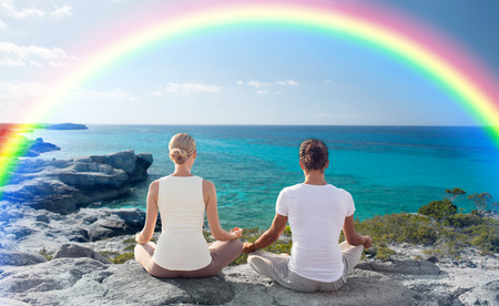 fitness, sport, people, yoga and lifestyle concept - happy couple meditating in lotus pose on summer beach from back photo