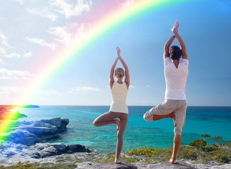 fitness, sport, people, yoga and lifestyle concept - happy couple meditating in tree pose on summer beach from back Фото со стока
