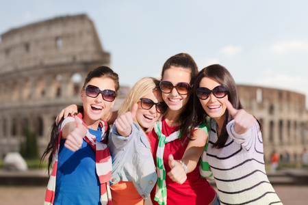 frienship: summer holidays, vacation, travel, friendship and people concept - happy teenage girls or young women in sunglasses showing thumbs up and laughing over coliseum background Stock Photo