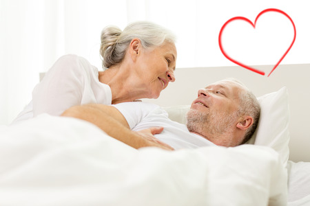 family, bedtime, valentines day, love and people concept - happy senior coupler lying in bad and talking at home with red heart shape photo