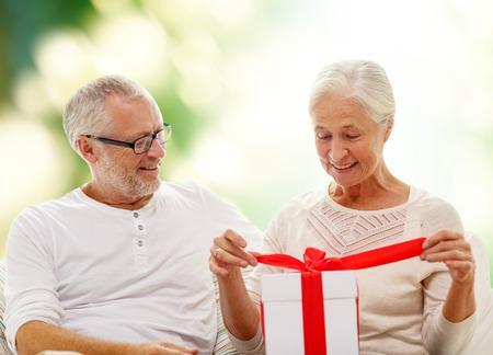 vejez feliz: familia, d�as de fiesta, la edad y el concepto de la gente - la feliz pareja senior con caja de regalo sobre fondo verde