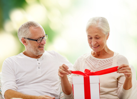 happy old age: family, holidays, age and people concept - happy senior couple with gift box over green background