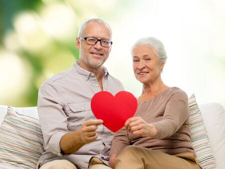 family, holidays, age and people concept - happy senior couple holding little red paper heart shape cutout and sitting on sofa over green background Banque d'images