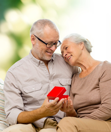 family, holidays, age and people concept - happy senior couple with little red gift box over green background photo