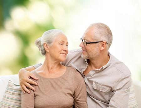 vejez feliz: la familia, las relaciones, el amor, la edad y el concepto de la gente - la feliz pareja senior abrazos y mirando el uno al otro en el sofá sobre fondo verde Foto de archivo