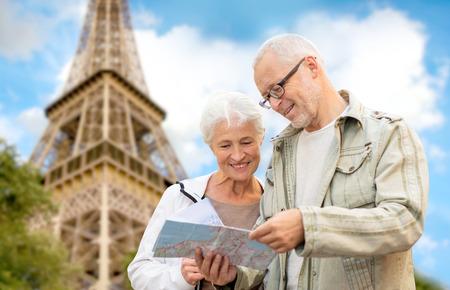 familie, leeftijd, toerisme, reizen en mensen concept - senior paar met kaart en stadsgids over de Eiffeltoren en de blauwe hemel achtergrond