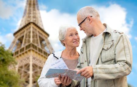 familiar, la edad, el turismo, los viajes y el concepto de la gente - pareja de ancianos con el mapa y guía de la ciudad sobre la torre Eiffel y el cielo azul de fondo