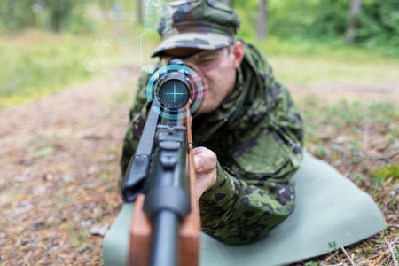infantryman: hunting, war, army, technology and people concept - close up of young soldier or sniper holding gun with virtual screen projection and aiming in forest